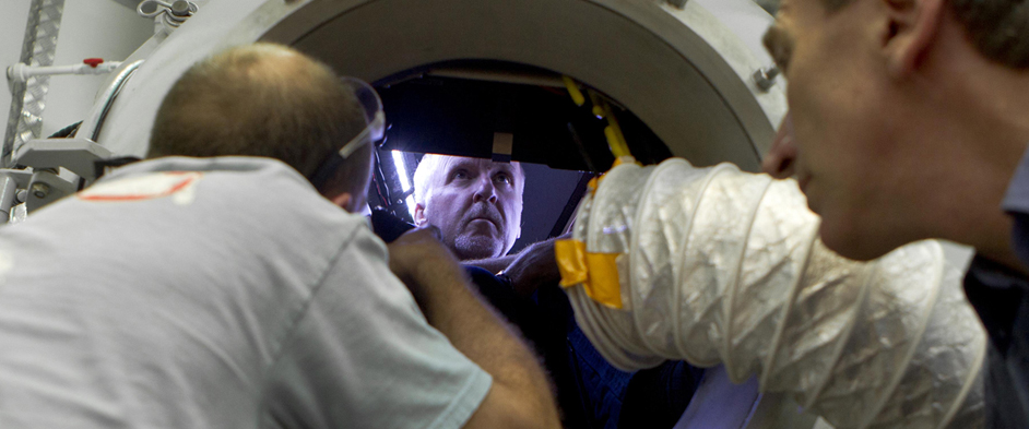 Photo: James Cameron, center, inside the pressure sphere simulator
