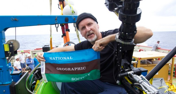 Photo: James Cameron holds a National Geographic Society flag
