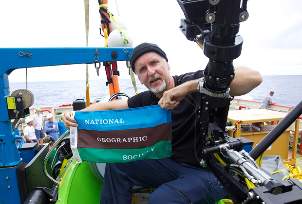 <em>Photo by Mark Thiessen/National Geographic</em><br> Cameron holds the National Geographic Society flag after successfully completing the first ever solo dive to the bottom of the Mariana Trench. The dive was part of <em>DEEPSEA CHALLENGE</em>, a joint scientific expedition by Cameron, the National Geographic Society, and Rolex to conduct deep-ocean research.