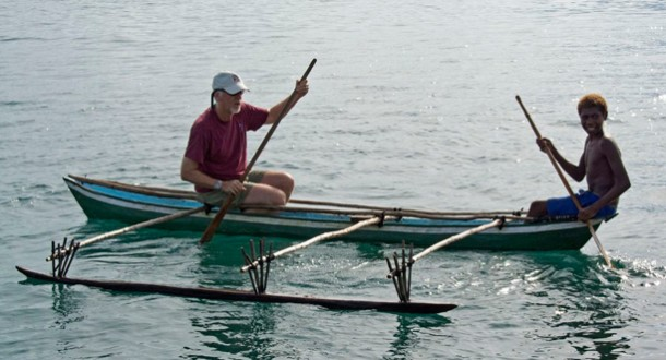 Photo: James Cameron and a young Papua New Guinean paddle a canoe