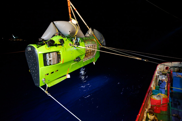 <em>Photograph by Mark Thiessen/National Geographic</em><br>The <em>DEEPSEA CHALLENGER</em>, carrying Cameron, is hoisted into the Pacific Ocean on its way to the Challenger Deep, the deepest part of the Mariana Trench.