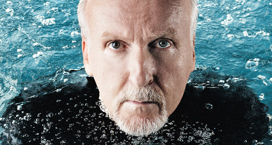 Picture of the close-up face and eyes of James Cameron rising from blue water