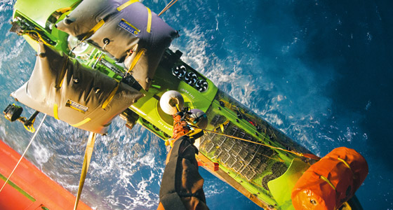 Picture of the Deepsea Challenger being lowered to the ocean surface